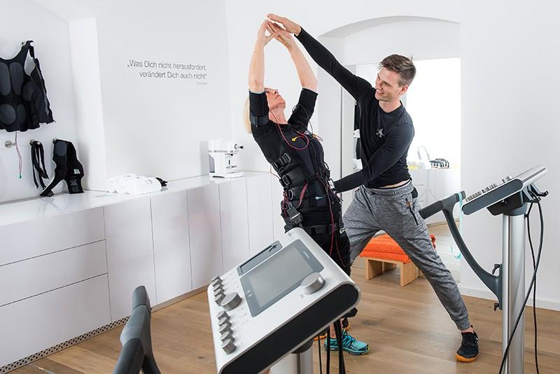Der Personal Trainer achtet beim EMS Training auf die perfekte Ausführung